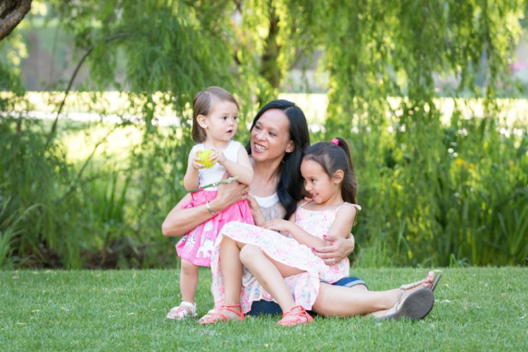 Family photoshoot - Two young daughters sitting on their mothers lap in a beautiful green park.