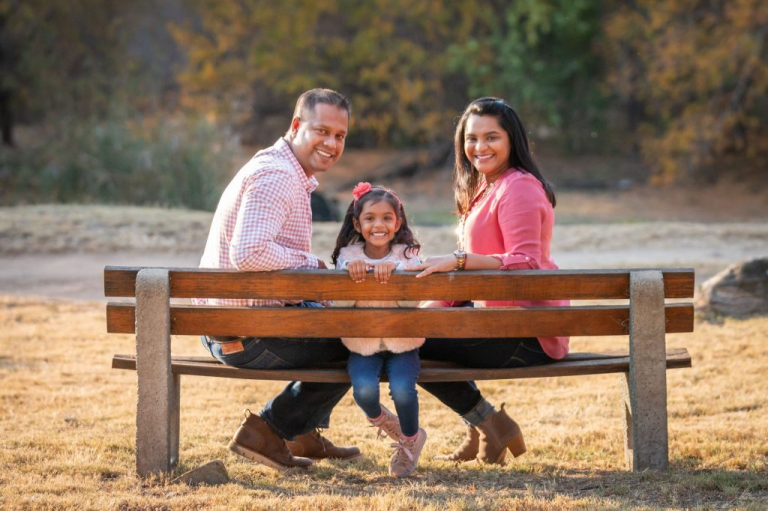 Family photoshoot - Parents and young daughter sitting on a bench in a park