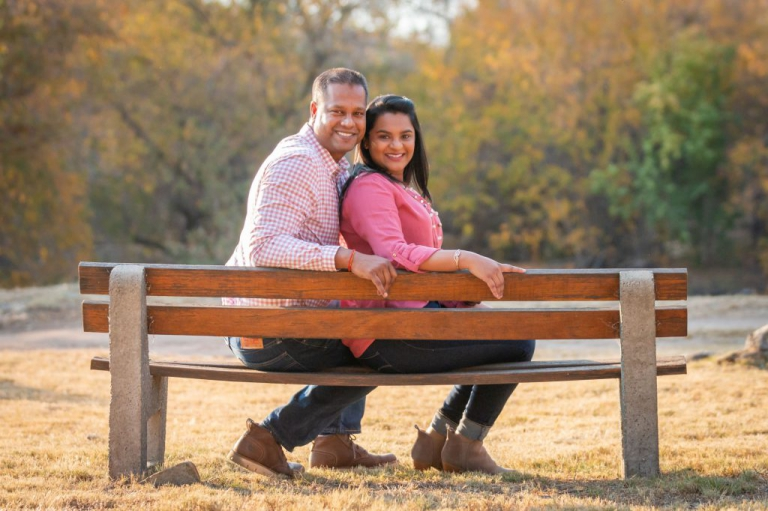 Family photoshoot - Husband and wife sitting on a fence in a park