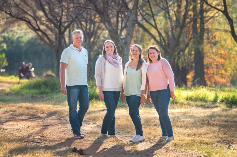 Family photoshoot - Family of four standing in a beutiful park, autumn colours