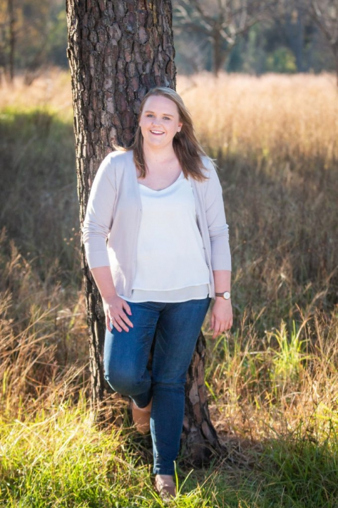 Family photoshoot - Young lady standing against a tree in the long grass of a veld.