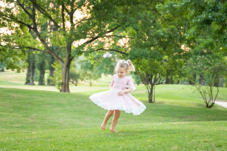 Family photo shoot - A little girl dancing in a green park at sunset