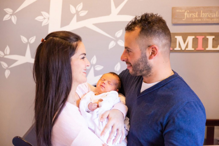 Newborn photoshoot - Mother and father holding newborn baby girl in nursery