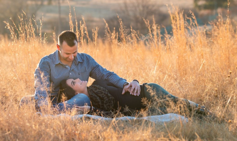 Maternity Photoshoot - Mommy to be lying on daddy's lap in field holding baby bump