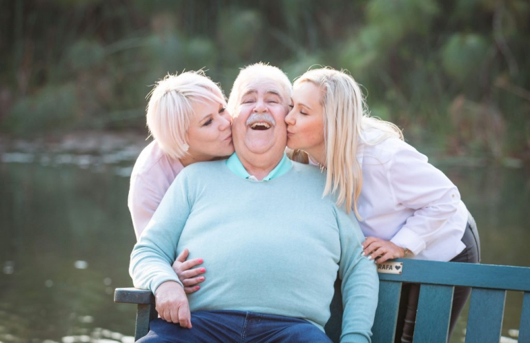 Family photo shoot - Father sitting on a bench in a beautiful park, while his two daughters kiss him on the cheek.